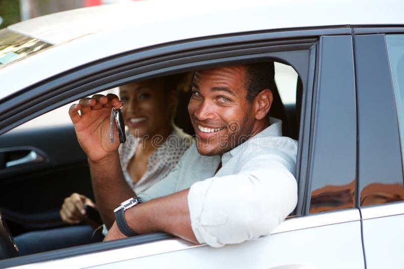 Sluit omhoog Afrikaanse Amerikaanse paarzitting in auto het glimlachen stock foto