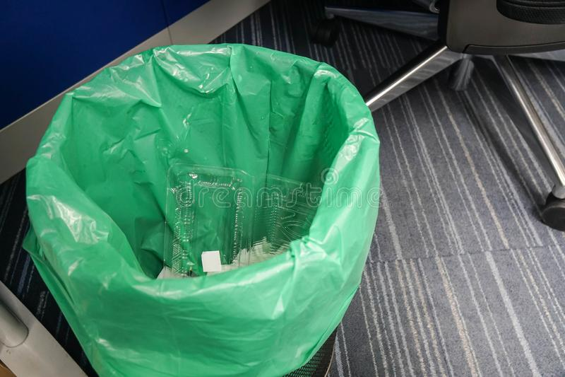Sluit omhoog afvalbak met groene plastic zak bij bureau royalty-vrije stock foto's