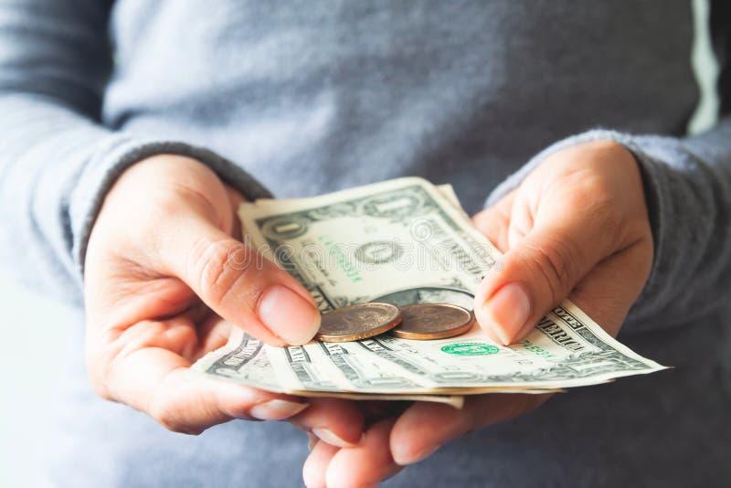 Sluit omhoog Amerikaanse dollarrekeningen en muntstukken op vrouwenhanden Zaken en stock foto