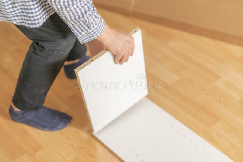Sluit omhoog arbeidershand assemblerend het nieuwe meubilair op de houten vloer in nieuw vlak h royalty-vrije stock foto