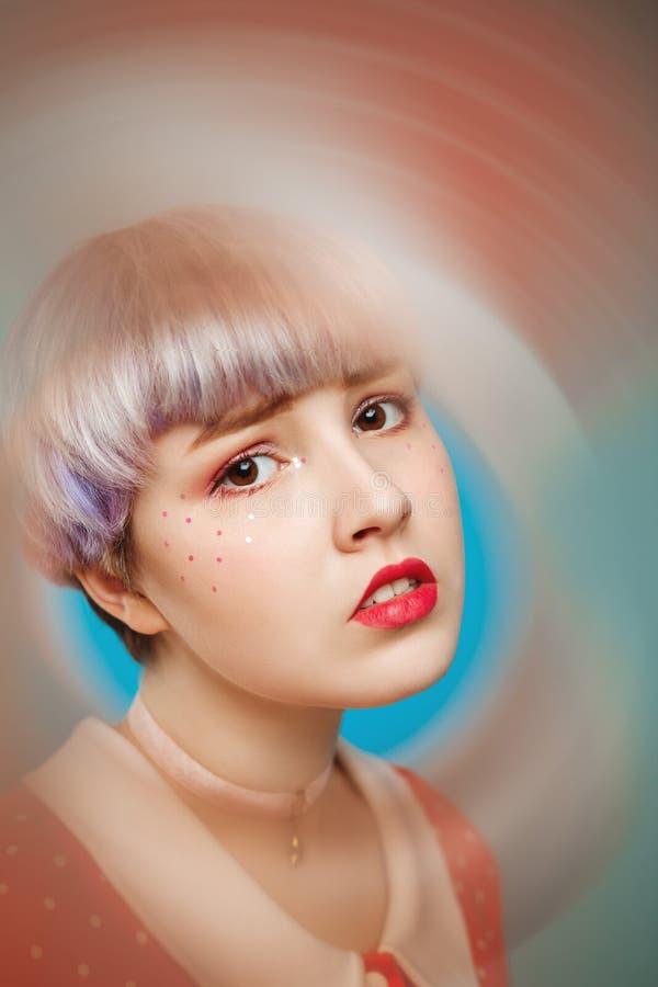 Sluit omhoog artistiek conceptueel portret van mooi dollishmeisje met kort licht violet haar die rode kleding over blauw dragen stock foto's