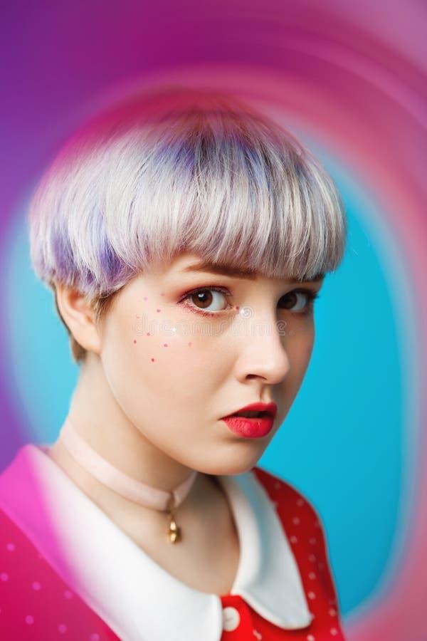 Sluit omhoog artistiek conceptueel portret van mooi dollishmeisje met kort licht violet haar die rode kleding over blauw dragen stock fotografie