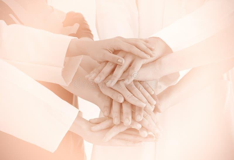 Sluit omhoog artsen en verpleegsters in een medisch team die handenthee stapelen royalty-vrije stock afbeeldingen