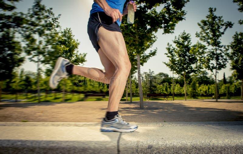 Sluit omhoog atletische benen van de jonge mens die in stadspark lopen met bomen op de zomer opleidingssessie het praktizeren spo stock foto