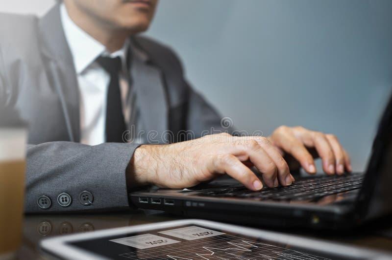 Sluit omhoog Aziatische Zakenman in grijs kostuum gebruikend en typend op lapt stock foto's