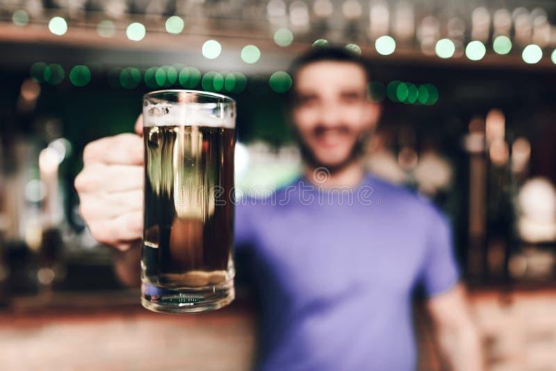 Sluit omhoog barmannen die glas bier houden bij sportenbar stock fotografie