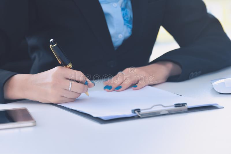 Sluit omhoog bedrijfsvrouwenhand ondertekenend contractdocument royalty-vrije stock afbeeldingen