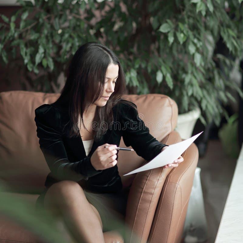 Sluit omhoog bedrijfsvrouwenzitting in bedrijfscentrum en lezingsdocumenten royalty-vrije stock foto's