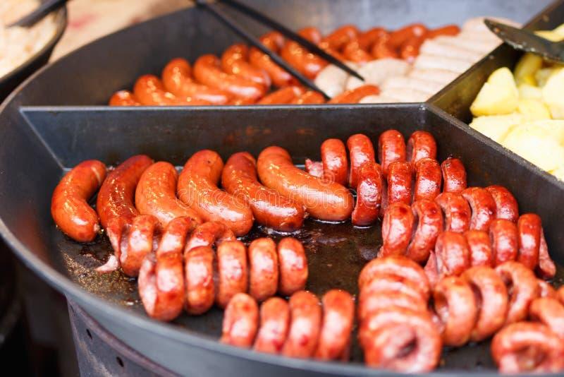 Sluit omhoog beeld heel wat smakelijke varkensvleesworsten en andere vlees het koken op een ronde vlakke grill Gebraden gesteunde royalty-vrije stock fotografie