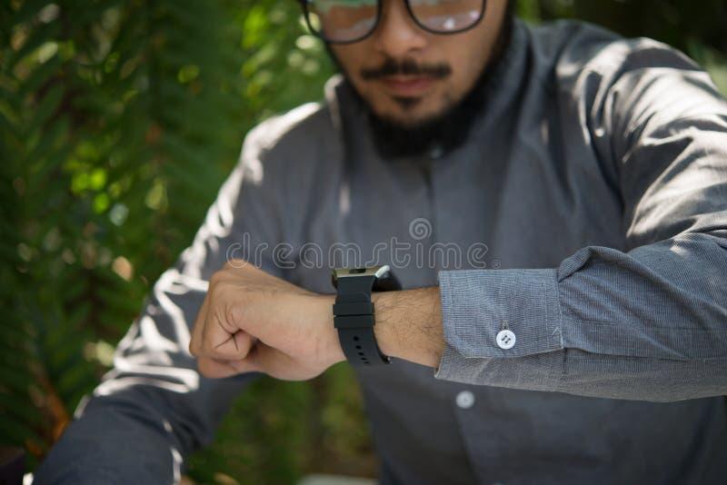 Sluit omhoog beeld van de jonge mens die zijn smartwatch bekijken stock foto's