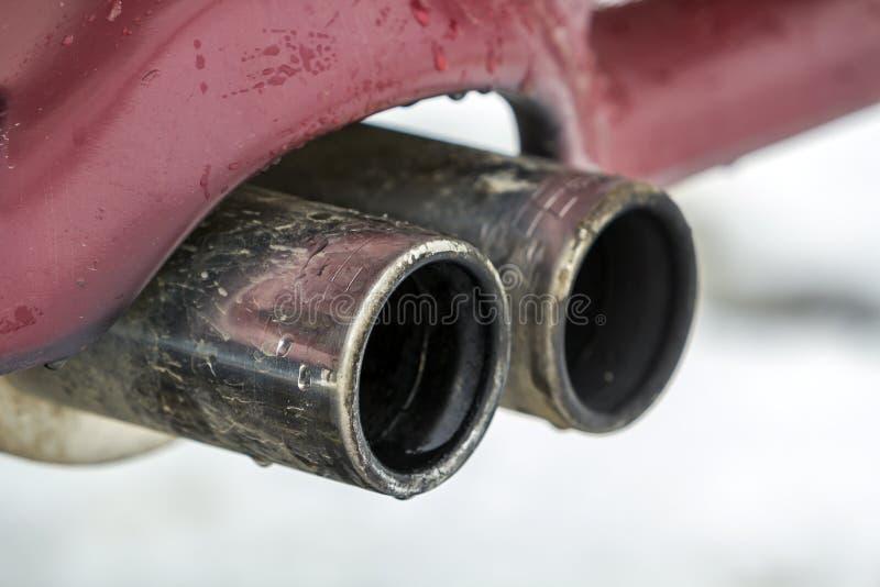 Sluit omhoog beeld van een auto dubbele uitlaatpijp Emissie van giftig koolmonoxidegas in atmosfeer, het concept van de milieuver royalty-vrije stock afbeeldingen