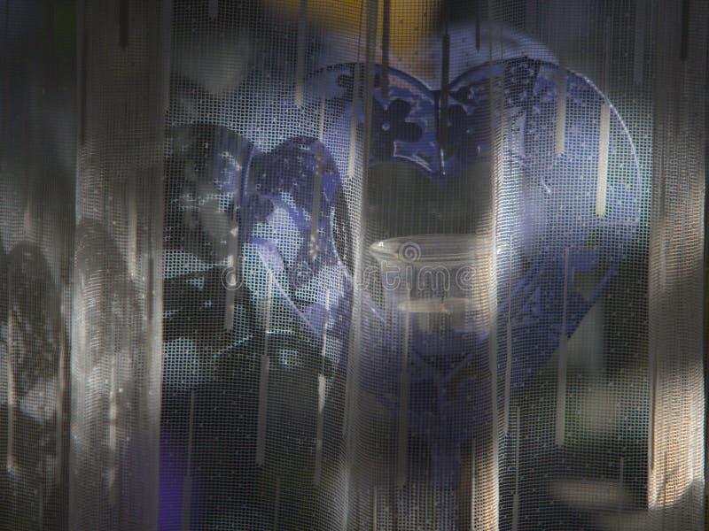 Sluit omhoog beeld van een purpere gekleurde hart-vormige kaarsenhouder achter netto gordijn Verloren liefdeconcept stock fotografie