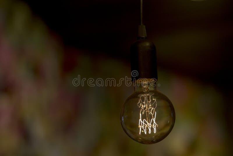 Sluit omhoog beeld van een stoffige retro stijl elektrische gloeilamp die een zwak licht in een donker binnenland verstrekken royalty-vrije stock foto's