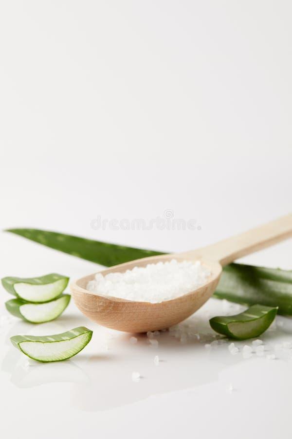 sluit omhoog beeld van houten lepel met zout, het blad van aloëvera en plakken op witte oppervlakte royalty-vrije stock foto's
