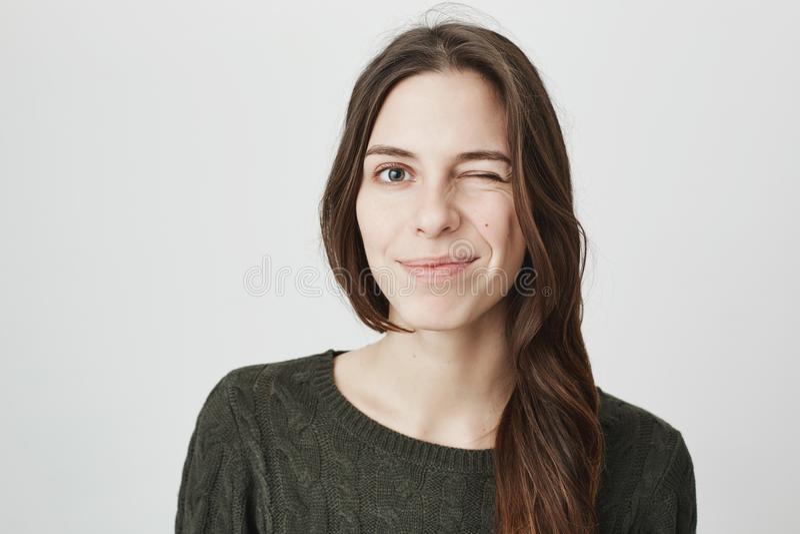 Sluit omhoog beeld van jong vrij Europees meisje in toevallige donkergroene sweater die en over witte achtergrond knipogen glimla royalty-vrije stock afbeelding