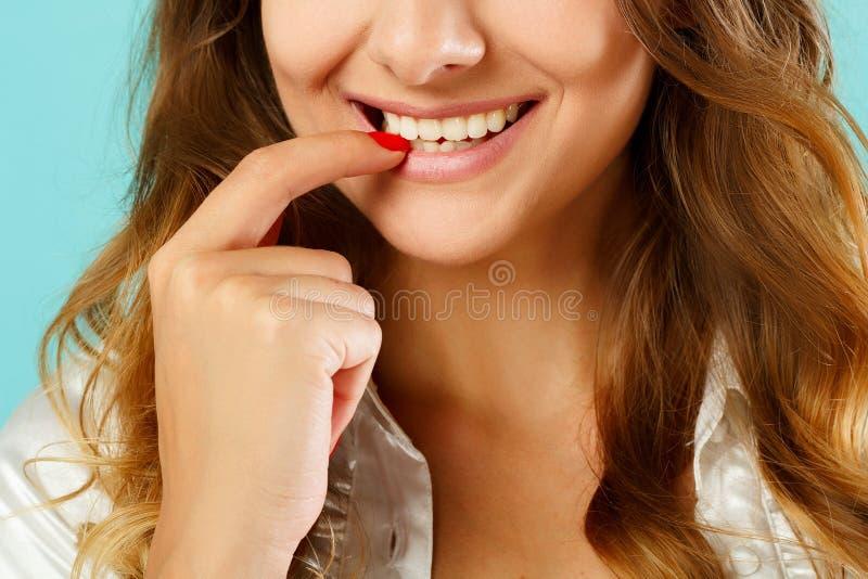 Sluit omhoog beeld van vrouwen` s glimlach over blauwe achtergrond stock afbeelding