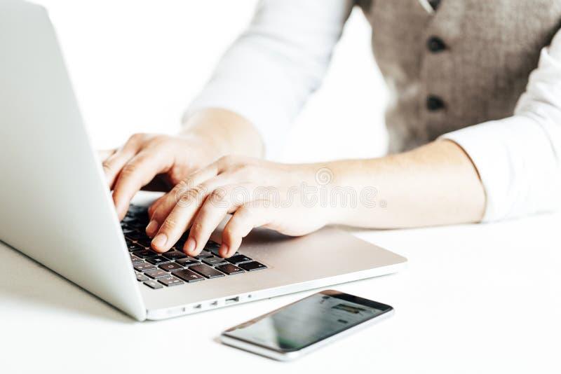 Sluit omhoog beeld van zakenman gebruikend laptop en een smartphone royalty-vrije stock foto's
