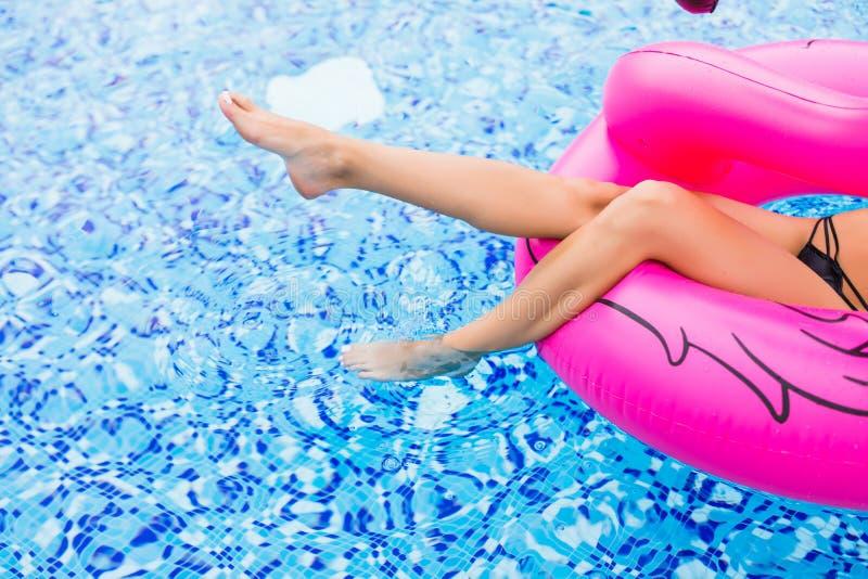 Sluit omhoog benen van schoonheids sexy meisje op roze flamingo in pool De zomerroeping stock afbeelding