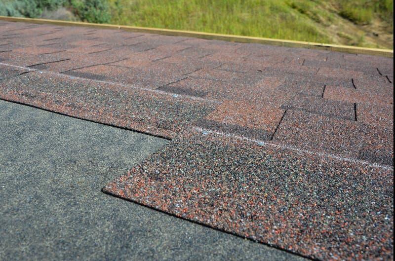 Sluit omhoog bij het installeren van daktegels, asfaltdakspanen Dakwerkbouw royalty-vrije stock afbeelding