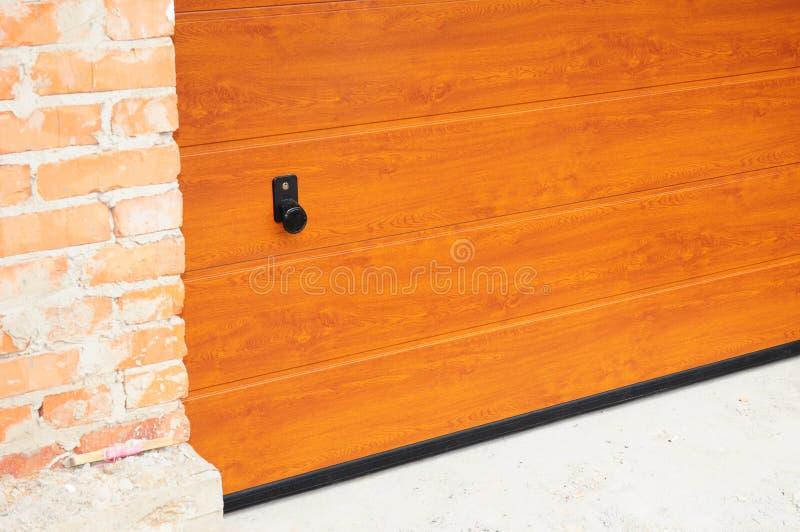 Sluit omhoog bij het installeren van de raad van de garagedeur in de nieuwe bouw van het baksteenhuis stock fotografie