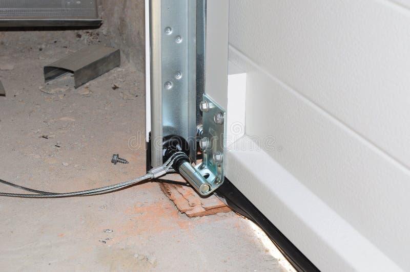 Sluit omhoog bij het Installeren van Garagedeur Het Postspoor van de garagedeur en de Lenteinstallatie royalty-vrije stock afbeelding