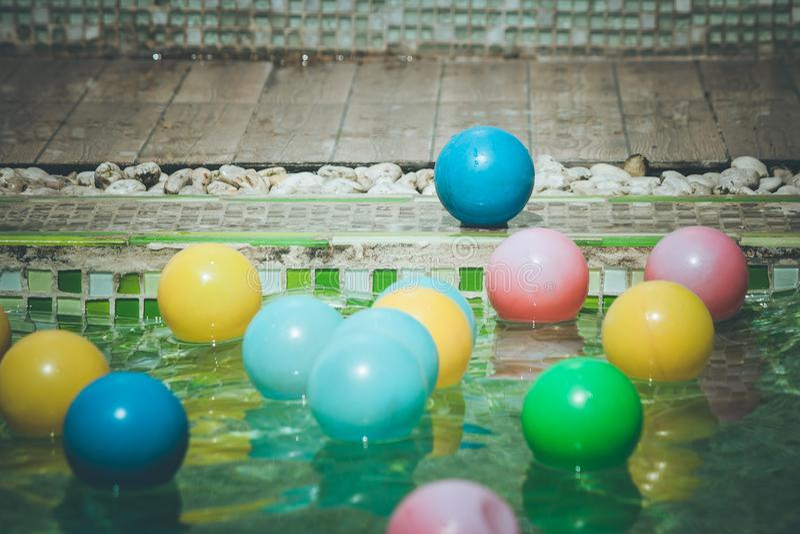 Sluit omhoog blauwe kleine bal op tegelvloer whith velen kleurrijke kleine bal in de poolvoorgrond in uitstekende stijl royalty-vrije stock foto's