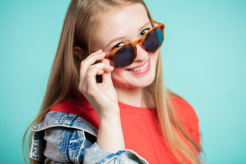 Sluit omhoog blij meisje bekijkt met een glimlach de camera terwijl het verminderen van haar zonnebril stock afbeeldingen