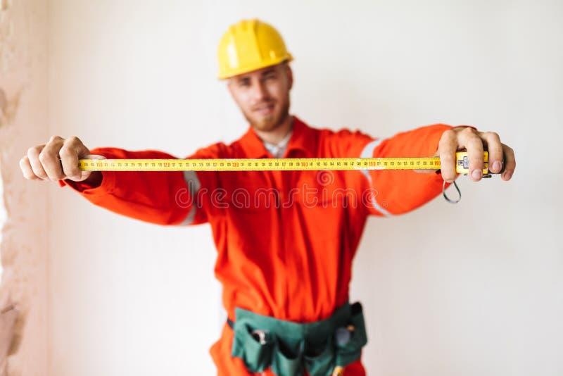 Sluit omhoog bouwer in de oranje het werkkleren en band van de bouwvakkerholding royalty-vrije stock fotografie