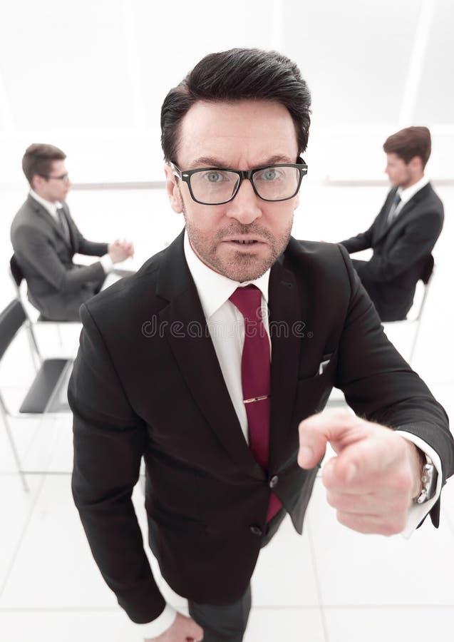 Sluit omhoog boze werkgever die op u richten stock foto