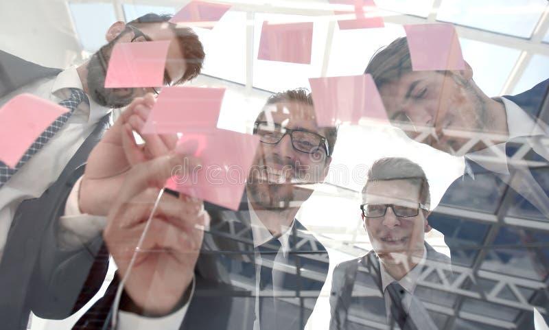 Sluit omhoog commercieel team die kleverige nota's over glas lezen royalty-vrije stock afbeelding