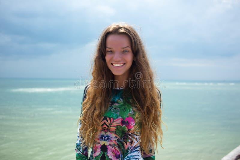 Sluit omhoog de aantrekkelijke schoonheid met het pluizige donkerbruine lange haar, de glimlach die cheerfully tijd aan een witte royalty-vrije stock fotografie