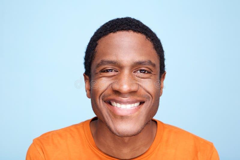 Sluit omhoog de Afrikaanse Amerikaanse mens die tegen blauwe achtergrond glimlachen stock afbeelding