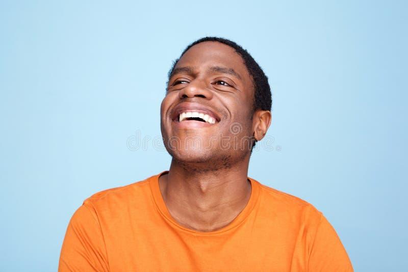Sluit omhoog de Afrikaanse Amerikaanse mens die tegen blauwe achtergrond lachen royalty-vrije stock afbeelding
