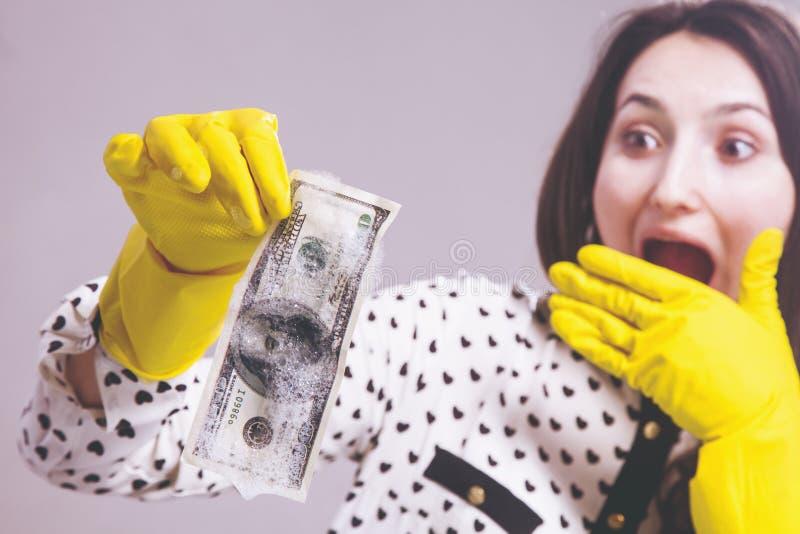 Sluit omhoog de Amerikaanse dollarrekening van vrouwenwassen als symbool van het witwassen en legalisatie van geld Selectieve nad stock afbeeldingen