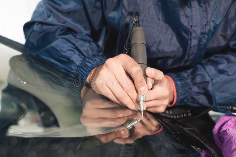 Sluit omhoog de arbeider die van de Autoglans en een windscherm of windscherm van een auto bevestigen herstellen bij een garagebe stock foto