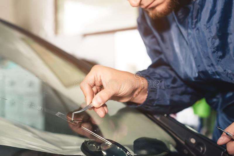 Sluit omhoog de arbeider die van de Autoglans en een windscherm of windscherm van een auto bevestigen herstellen bij een garagebe royalty-vrije stock afbeeldingen
