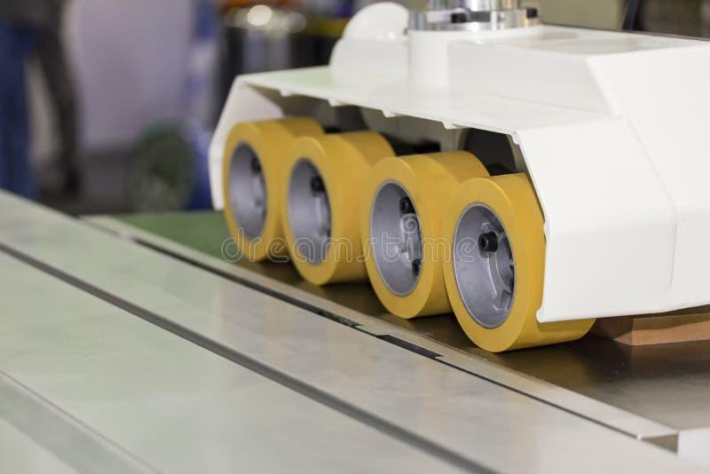Sluit omhoog de automatische voeder van de wielmacht voor de machine van de het paneelsnijder van de houtbewerkingsrouter voor in stock fotografie