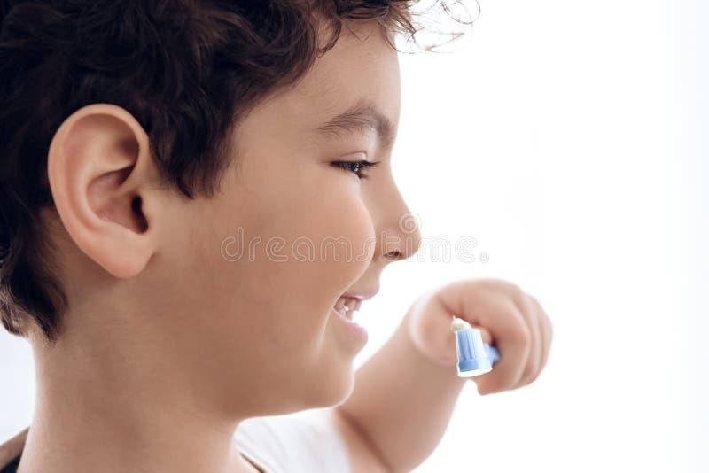 Sluit omhoog De blije jongen borstelt tanden met tandpasta op witte achtergrond royalty-vrije stock fotografie