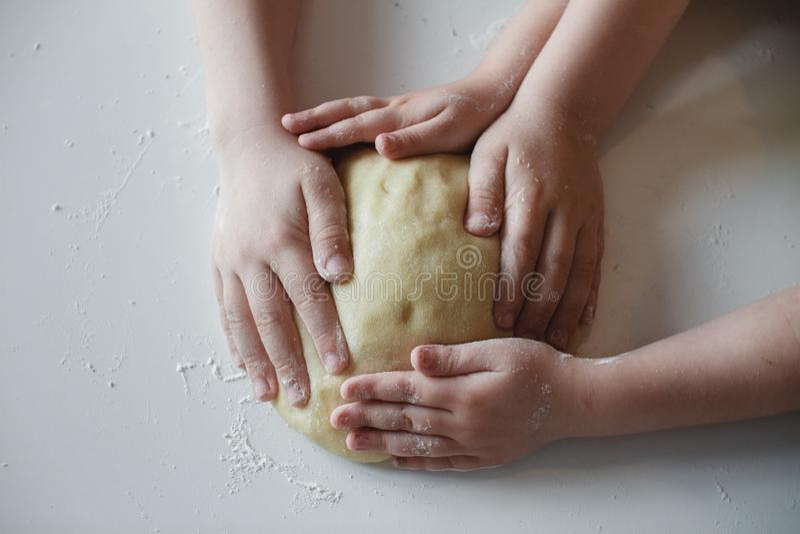 Sluit omhoog De handen van vier kinderen, die het deeg drukken aan de witte lijst Voorbereiding van desserts royalty-vrije stock afbeeldingen