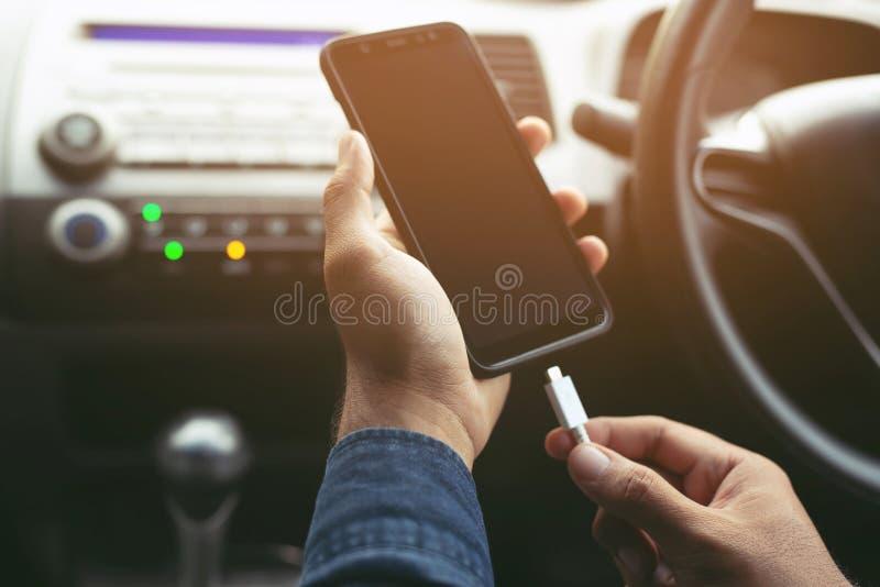 Sluit omhoog de holdingslast van de mensenhand de batterij mobiele smartphone in auto Verlofruimte om berichten te schrijven stock foto