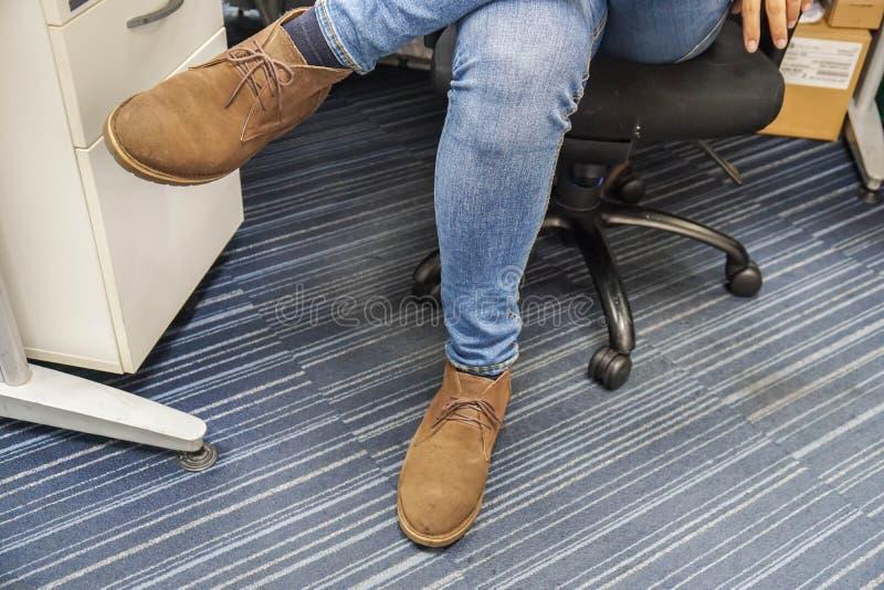 Sluit omhoog de jeans van de mensenslijtage en de bruine leerschoenen zitten en kruisen zijn benen op bureaustoel royalty-vrije stock foto