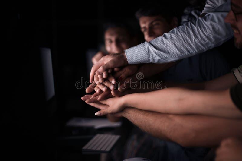 Sluit omhoog de jonge actieve beambten houden samen hun handen stock foto's