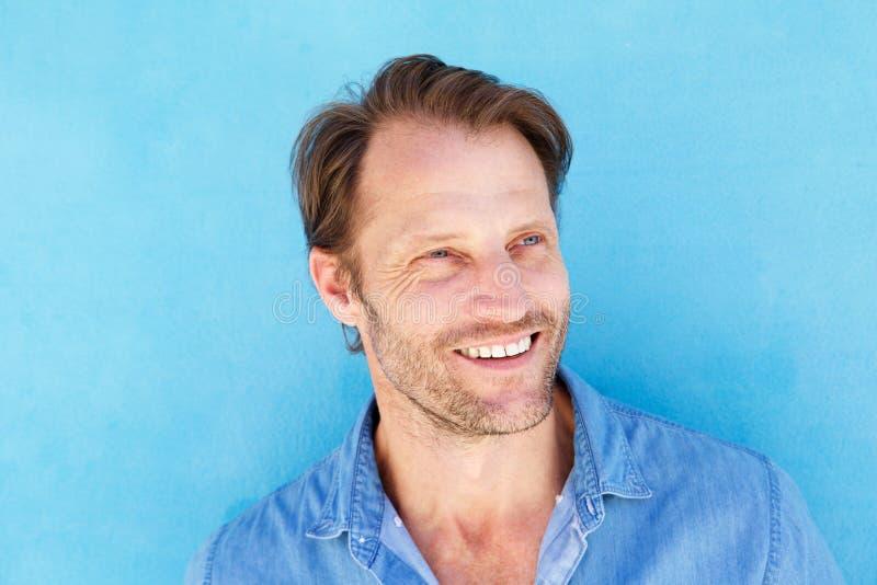 Sluit omhoog de knappe oudere mens die tegen blauwe muur glimlachen royalty-vrije stock fotografie