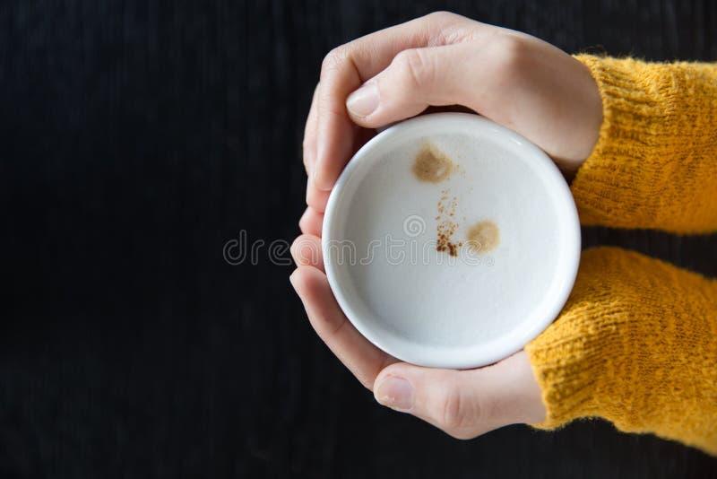 Sluit omhoog de kop van de Vrouwenholding van hete koffie op donkere houten lijst stock fotografie