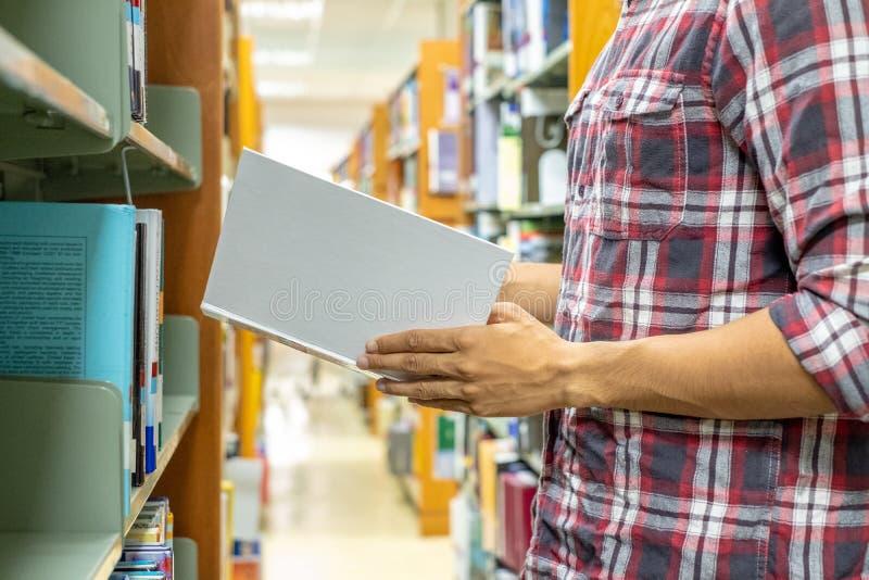Sluit omhoog de mensen die van de handstudent boek voor lezing in bibliotheek vinden Het concept van het onderwijs stock afbeelding