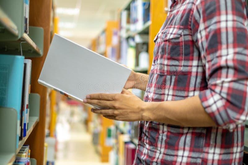 Sluit omhoog de mensen die van de handstudent boek voor lezing in bibliotheek vinden Het concept van het onderwijs royalty-vrije stock foto