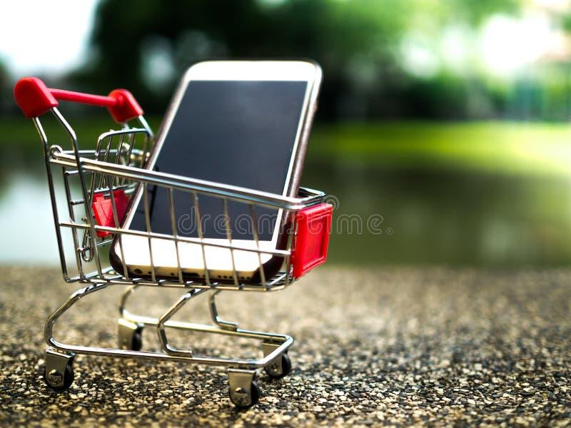 Sluit omhoog de mobiele telefoon in boodschappenwagentje, zaken in elektronische handelconcept royalty-vrije stock afbeeldingen