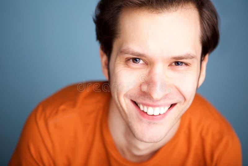 Sluit omhoog de modieuze mens die op blauwe achtergrond glimlachen stock foto's