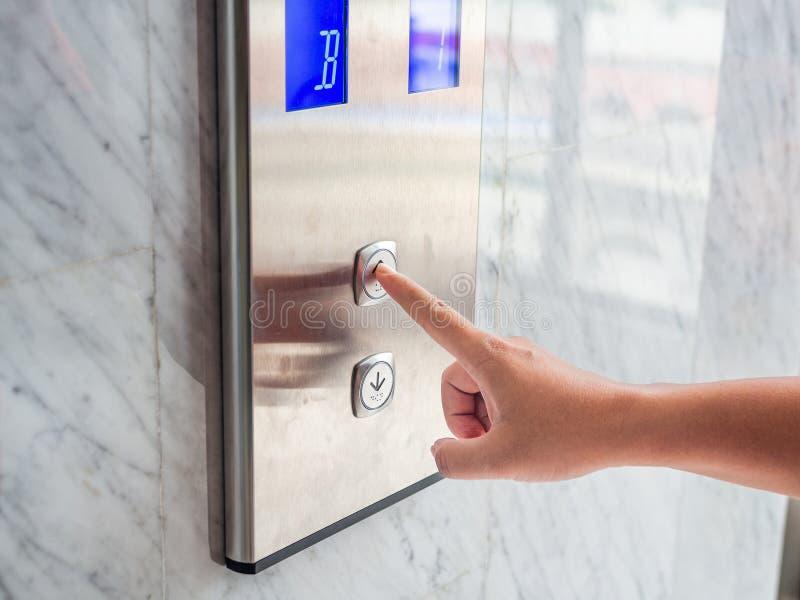 Sluit omhoog de pers van de mensenhand een omhooggaande knoop van lift binnen de bouwstijl royalty-vrije stock afbeelding