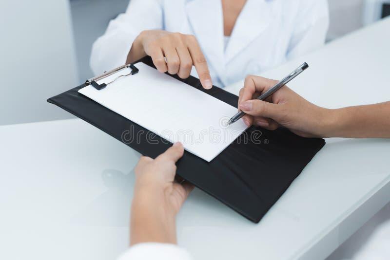 Sluit omhoog De secretaresse in een medische kliniek helpt geduldige volledig de noodzakelijke vormen alvorens behandeling te beg stock foto